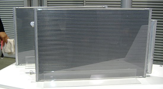 Lightweight, thin condenser for air conditioners, foreground, with conventional condenser, background